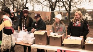 young kids helping gather items at a high school charity drive